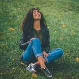 Beautiful young girl with curly hair sitting on green in the park and laughing