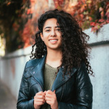 Beautiful young girl with curly hair in the autumn street