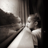 Little cute daughter Traveling by train . Small girl sitting near window and watching rain drops