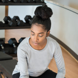 Young woman with a dumbbell in hand exercising on a bench at the gym