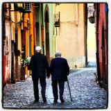 Old couple walking through an old village.