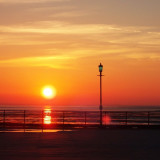 Flaming golden sunset at the British seaside, with vintage lamp post.