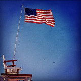 This lifeguard tower no longer exists. Amazing capture of a San Diego icon, with the American Flag and two F-15 fighter jets in formation in the deep blue California sky!