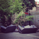 Cat napping on abandoned sofa in urban car park Peckham London.