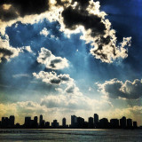 Looking at Hoboken, New Jersey from across the Hudson River on the island of Manhattan, NYC. A beautiful majestic sun is shining on Earch and you can see the heavenly rays penetrating the thick fluffy clouds.