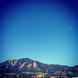 The majestic half supermoon overlooking the flatirons in the City of Boulder, Colorado.