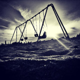 A black and white sunset with swings right in the middle of it