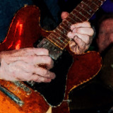 A close up photograph of a guitar being played digitally altered for an artistic effect.