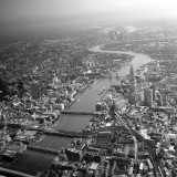 On approach into London City Airport which can be seen in the distance. A view of the Thames winding past London bridge, the Shard and on into the city. Black and white filter.