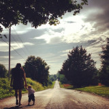 Mother and child walking down an old dirt road.