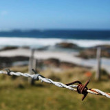 Close up of rusty barbed wire on a fence on Tiree, off Scotland. In the background is a deserted beach and the very blue sea on a windy day, taken when on holiday in May.