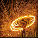 Person creating light trails with steel wool.