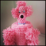 A crochet pink poodle toilet roll cover made from a vintage pattern