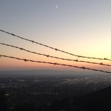 A view of the San Fernando Valley from the Starlight bowl in Burbank California. U love the moon on top and the barbed wire running across the picture.