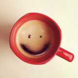 Good morning! Smiley happy face formed by foam in a red coffee cup.