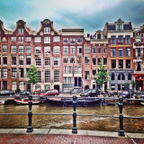 Row of houses in Amsterdam and a busy canal full of houseboats.
