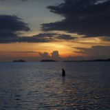 A long fisherman wades in the water on Sunset beach, Haad Rin, Thailand