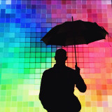 Man standing with an umbrella in front of a colorfully lit wall