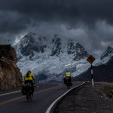 Cyclists with view toward Mount Huascaran, the highest peak in Cordillera Blanca, Peru