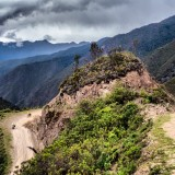 Cyclists on gravel road going downhill, Peru