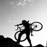 Woman carrying a bicycle