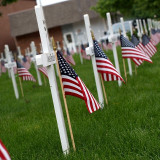 Miniature crosses and US flags adorn a courthouse lawn to honor fallen veterans of military service.