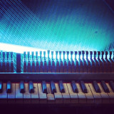 An old broken piano lit by blue neon light