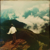 Man standing on a mountain and looking down at landscape