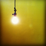 A light hanging in front of a yellow wall.