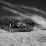 A windy day at Dungeness, the decrepit, old fishing boat struggles through a sea of grass.