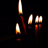 Burning candles against black background