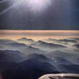 View of mountains in mist from airplane
