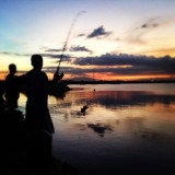 Silhouette of people fishing at sunset