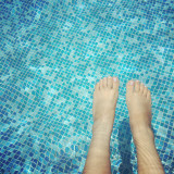 Human feet in swimming pool