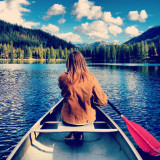 Rear view of woman paddling in lake