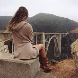 Woman sitting at the end of a bridge