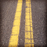 Tarmac road with yellow line, close-up