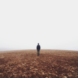 Lonely man standing on barren land