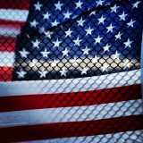 American flag from behind and shadow of chain-link fence