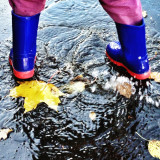Young boy in Wellies splashing in puddles in the rain