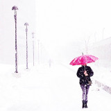 Woman with umbrella on sidewalk in winter