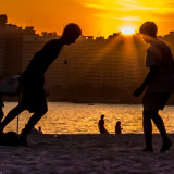 Teenage boys playing on a beach at sunset
