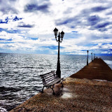 Bench and electric lights on jetty in sea