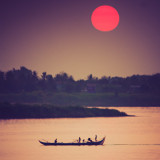 Silhouette of traditional fishermen, red sun