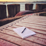 Writer's place: a notebook and a pen on a wooden bench