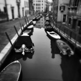 Silence and poetry of the Venice canals, palaces, houses and boats in a winter atmosphere, black and white photography