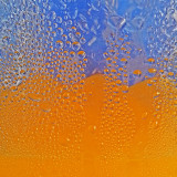 Orange juice in a pitcher with a blue backdrop.