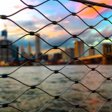 City viewed through a wire fence