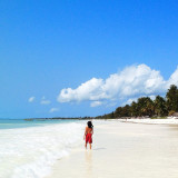 My son with all the space in the world at Paje Beach, Zanzibar. Fine white sands, blue skies, aqua seas and red shorts.