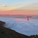 Golden Gate Bridge at sunset with fog and rising moon.
